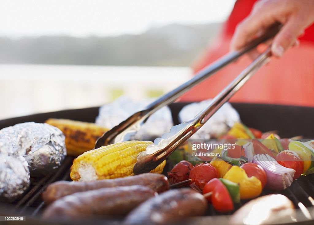 Close up of man grilling food on barbecue : Stock Photo