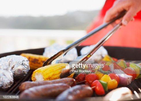 ている男性のクローズアップのバーベキューグリル料理