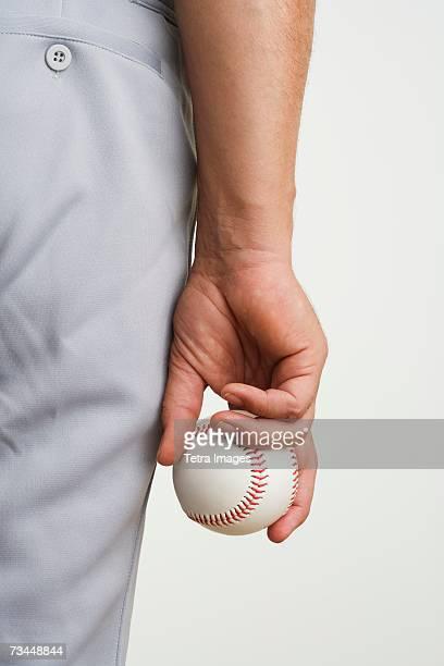 Close up of man holding baseball at side