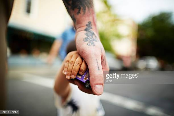 Close up of man holding boys hand and toy crossing road