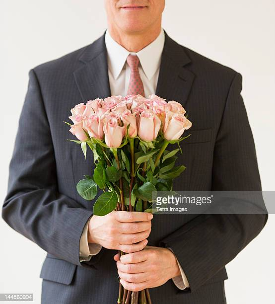 Close up of man in suit holding bouquet of roses, studio shot