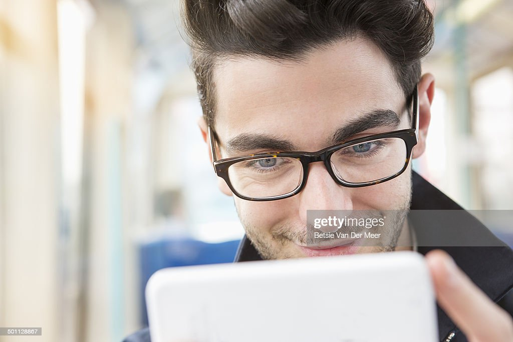 Close up of man looking at mobile phone in train. : ストックフォト