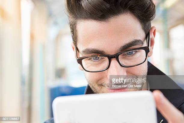 Close up of man looking at mobile phone in train.