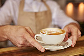 Close up of man serving coffee at cafe. Focus on male hands placing a cup of coffee on wooden counter.