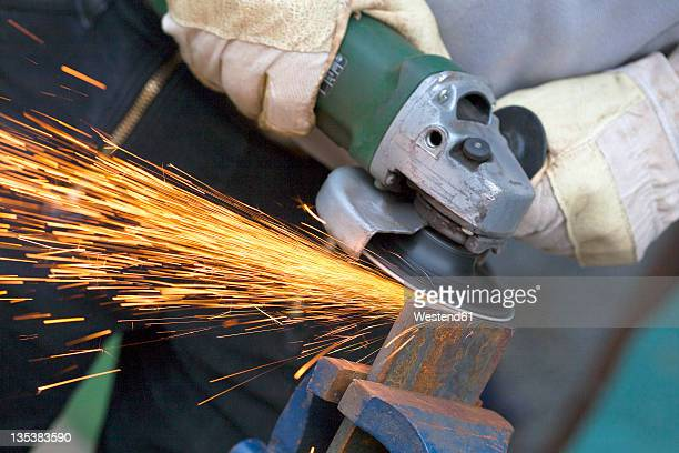 Close up of man sharpening piece of iron with angle grinder