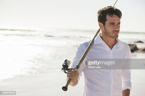 Close up of man with fishing rod on beach