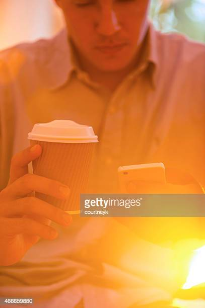 Close up of man with mobile phone and coffee.