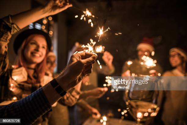 Close up of man's hand holding sparkler during a party with his friends.