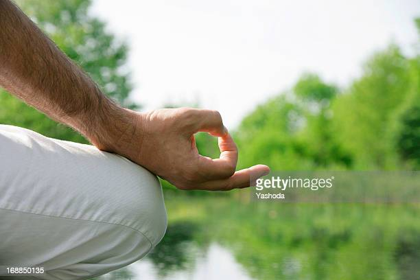 Close up of mans hand in meditation
