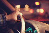close up of man's hand on steering wheel at night