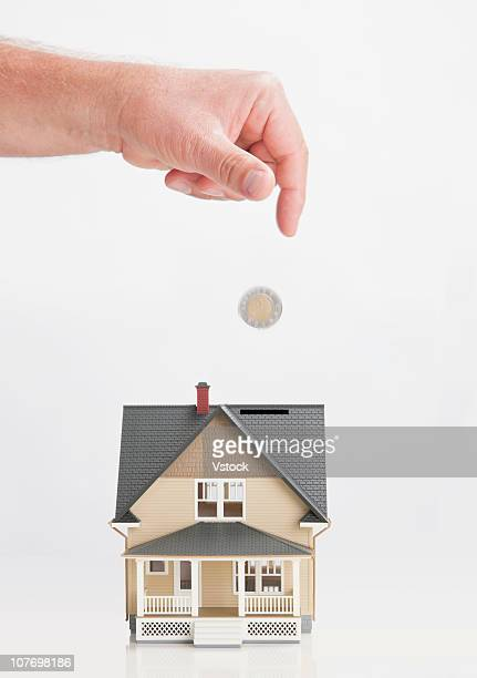 Close up of man's hand throwing coin into model house