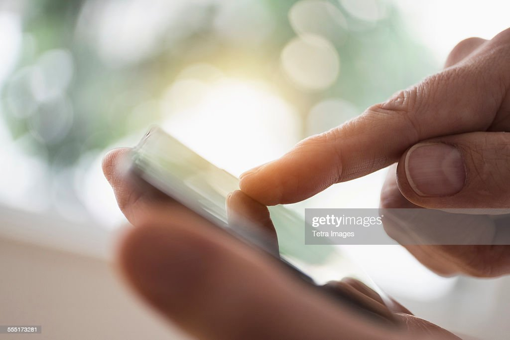 Close up of mans hand using smartphone