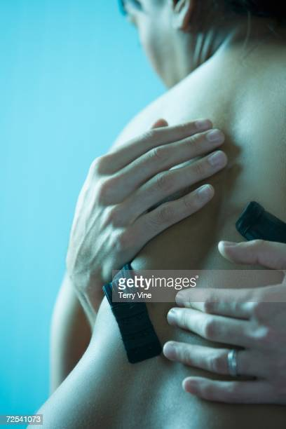 Close up of man's hands on woman's bare back with bra unhooked