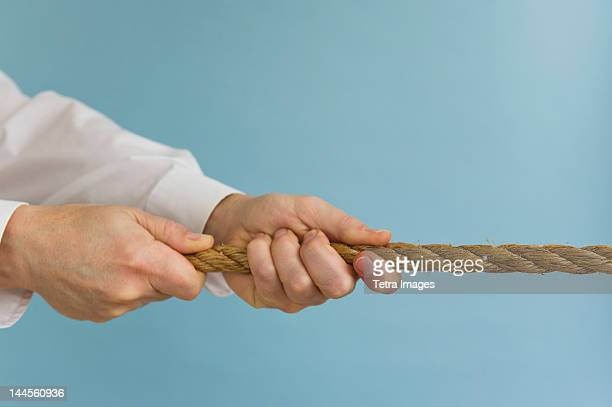Close up of man's hands pulling rope, studio shot