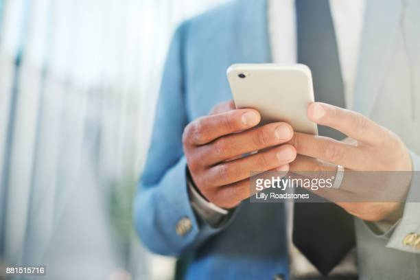 Close up of man's hands using mobile phone in pleasant city environment