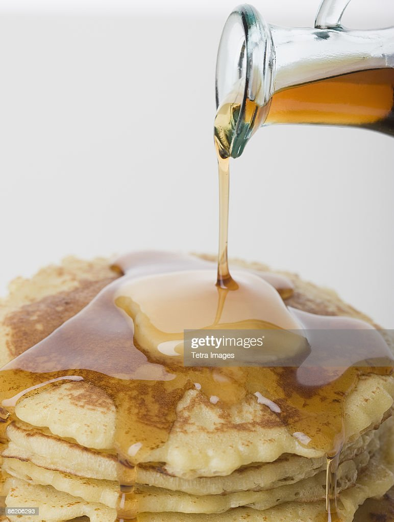 Close up of maple syrup being poured on pancakes : Stock Photo