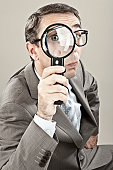 Close up of mature businessman looking through magnifying glass against grey background