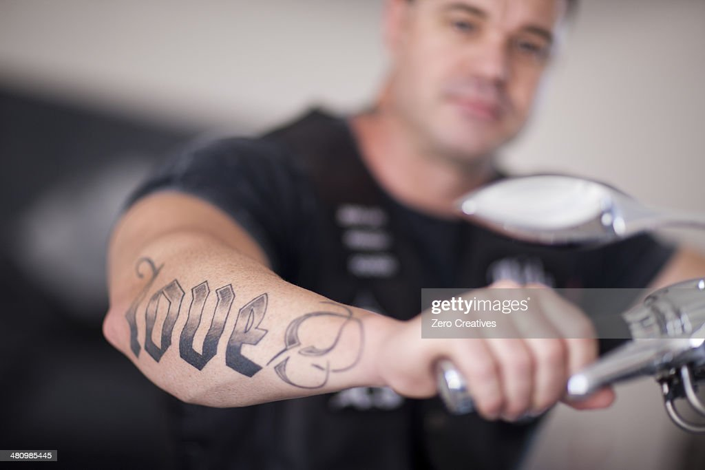Close up of mature man sitting on motorcycle indoors : Stock Photo