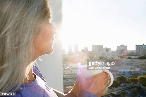 Close up of mature woman drinking coffee on city apartment balcony