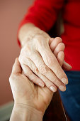 Close up of mature woman holding 82 year old grandmothers hand