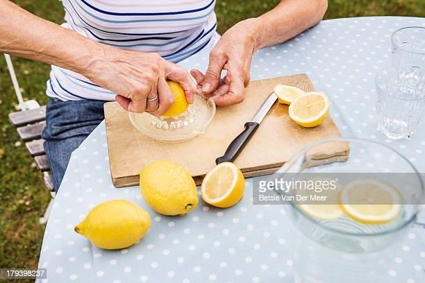 Close up of mature woman making lemonade.