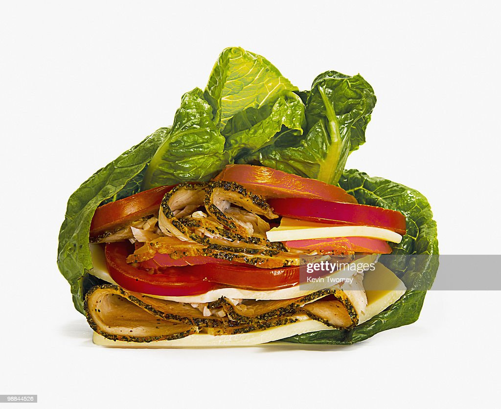 Close up of meat, tomatoes and cheese wrapped in lettuce : Stock Photo