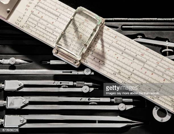 Close up of mechanical calculating ruler and set of drawing compasses.