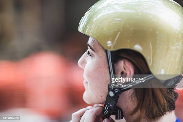Close up of mid adult woman cyclist fastening cycle helmet