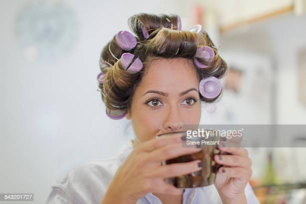 Close up of mid adult woman wearing hair rollers drinking coffee