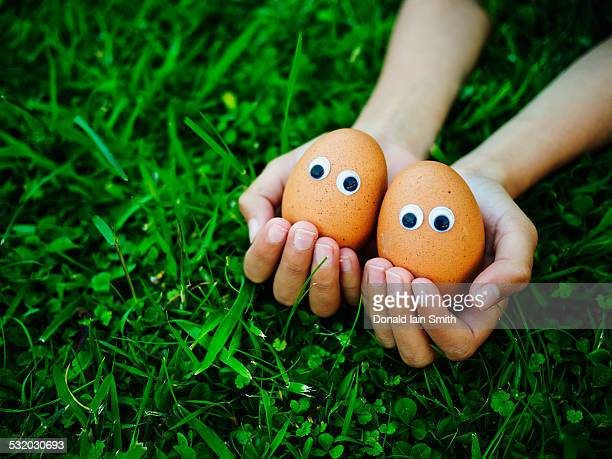 Close up of mixed race girl holding eggs with googly eyes