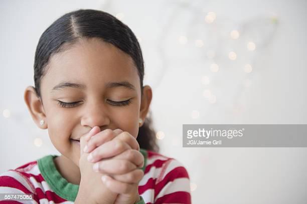 Close up of mixed race girl praying at Christmas