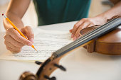 Close up of mixed race man writing sheet music for violin