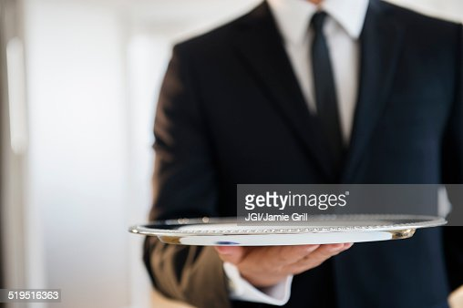 Close up of mixed race waiter holding empty tray