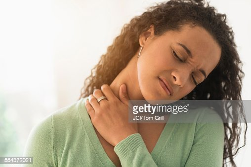 Close up of mixed race woman rubbing sore neck