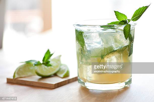 Close up of mojito glass with lemon slices blurred in back