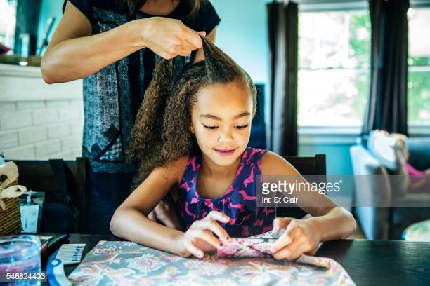 Close up of mother braiding hair of daughter