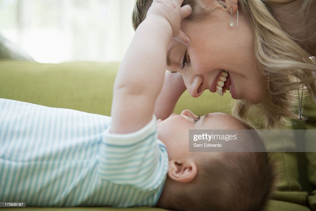 Close up of mother looking down at baby son : Stock Photo