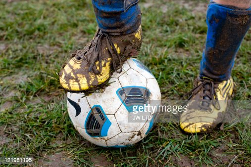 Close up of muddy football boot on football