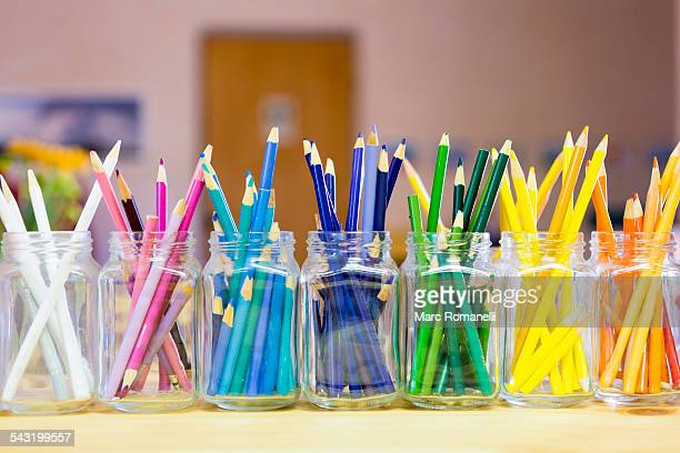 Close up of multicolor pencils organized in jars