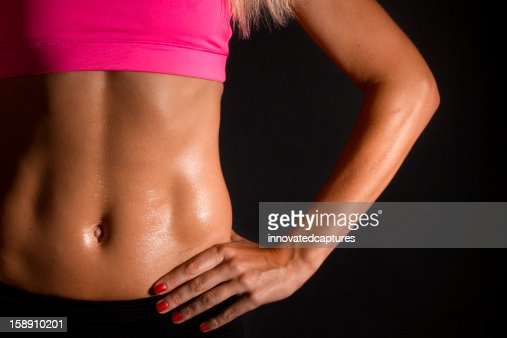 Close Up of Muscular Female Abs on Black Background : Stock Photo