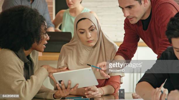 Close Up of Muslim Businesswoman Leading a Multi-Ethnic Team using Digital Tablet