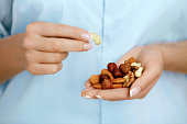 Close Up Of Nuts In Woman Hands. Female Holding Healthy Snacks. Healthy Lifestyle. Nutrition And Diet. High Quality Image.