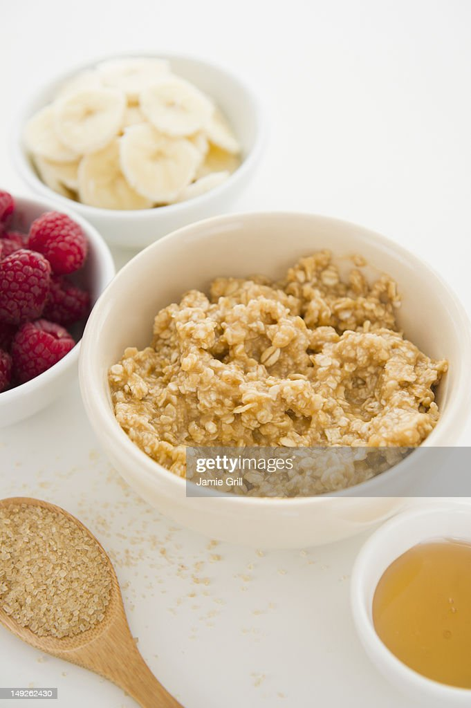 Close up of oats and fruits in bowls, studio shot : Stock Photo
