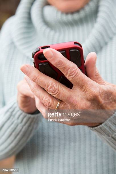 Close up of older Caucasian woman using cell phone