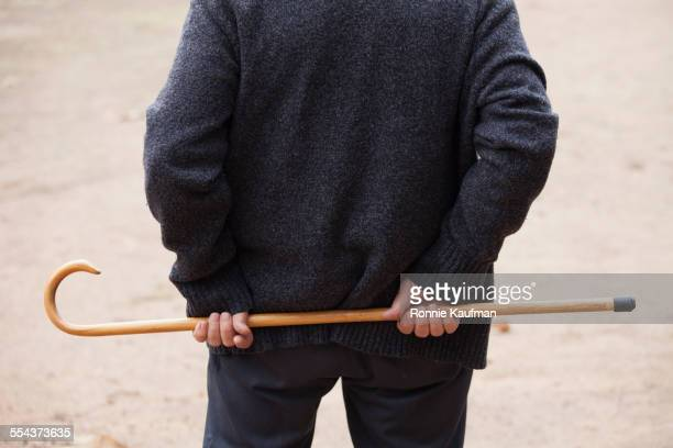 Close up of older man holding cane behind his back