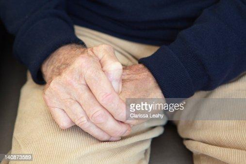 Close up of older mans folded hands