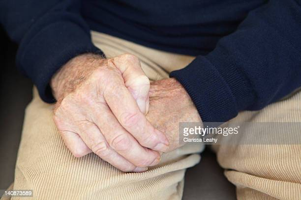 Close up of older mans folded hands