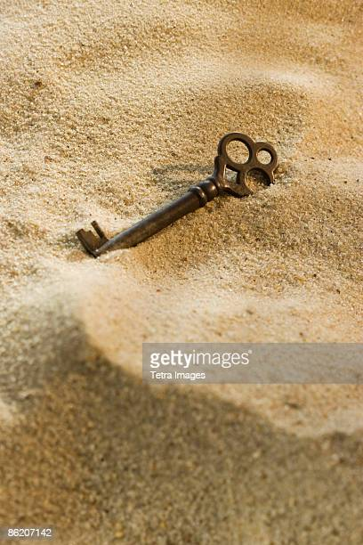 Close up of old-fashioned key in sand