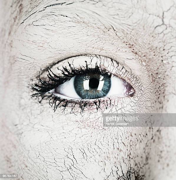 Close up of open eye and covered in dry mud