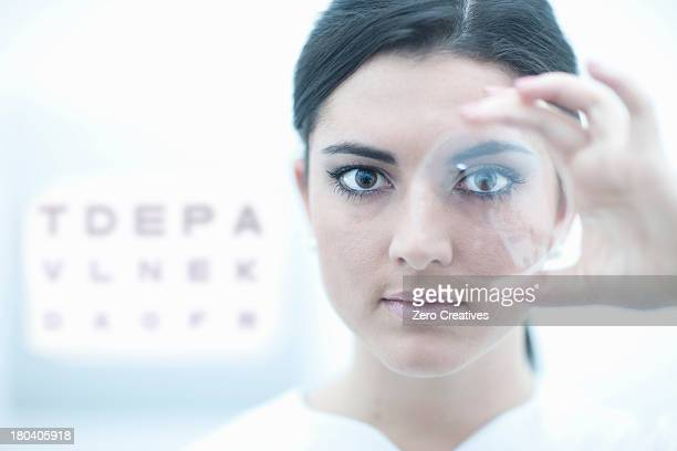 Close up of optician holding lens in eye clinic